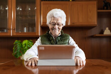 Friendly Elderly Female Showing Toothy Smile Against Tablet While Video Chatting In House
