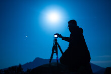 Side View Of Unrecognizable Male Traveler Silhouette With Photo Camera On Tripod Against Ridge Under Blue Sky With Shiny Sun At Night