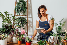 Cheerful Female Gardener In Apron Standing At Table With Various Potted Plants And Using Tablet While Working In Flower Shop