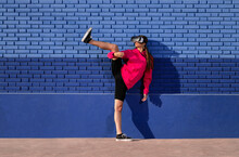 Fit Young Sportswoman In Sportive Outfit And Goggles Of Virtual Reality Raising Leg In Martial Kick Against Blue Brick Wall