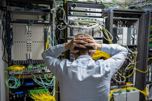 Back View Of Unrecognizable Male Technician Grabbing Head While Having Problem In Data Center With Server Racks