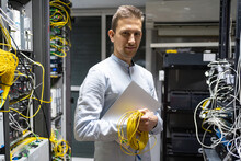 Positive Man In Wireless Headset Standing With Netbook And Cables In Server Room