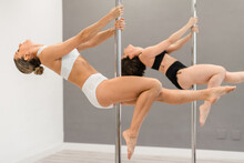 Side View Of Young Strong Female Athletes Leaning Back With Reached Legs While Dancing On Metal Poles In Studio