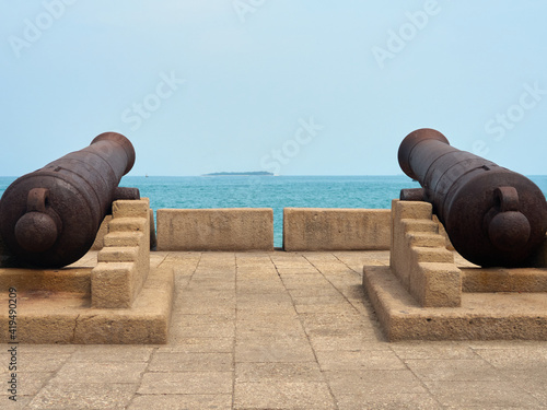 Canvas Print Close up view to two old powder cannons aiming to the open sea