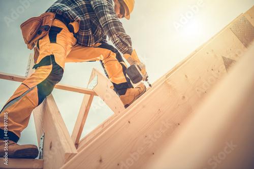 Fototapeta Carpenter Working on Wooden House Frame