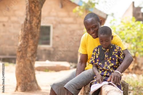 african man tutoring a child outside - fototapety na wymiar