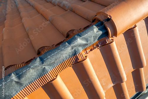 Fototapeta Closeup of yellow ceramic roofing ridge tiles on top of residential building roof under construction. obraz