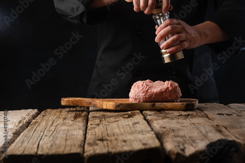 Vászonkép Chef prepares minced meat for making cutlet for burgers salt