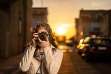 Joven Mujer Fotógrafa Con Una Cámara Réflex Negra Haciendo Una Foto Al Atardecer En Un Paisaje Urbano, Con Cazadora Blanca, Camiseta De Rayas, Al Atardecer