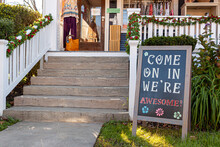"""A Sandwich Board With A Welcoming Notice On It Which Reads : """" Come On In, We Are Awesome """" Is Placed In The Front Yard Of A Small Local Clothing Shop In Historic Clifton, Virginia."""