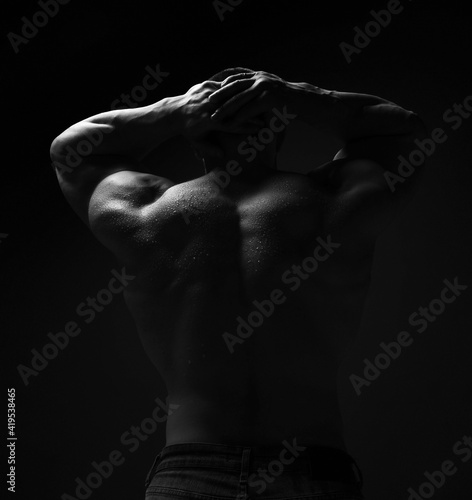 Canvastavla Muscular man, bodybuilder with wet athletic body is standing shirtless with his back to camera holding hands behind head over dark background