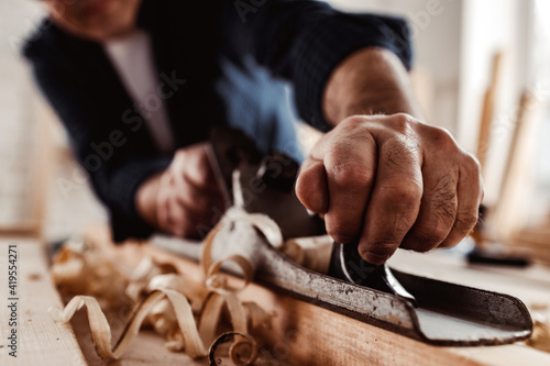 Leinwand Poster Carpenter's hands planing a plank of wood with a hand plane
