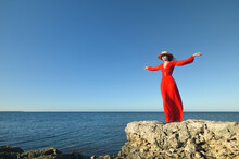 Portrait Of A Caucasian Young Woman In A Red Dress And Straw Hat On The Seashore. With His Arms Outstretched, He Stands On A Rock Looking At The Horizon. Hair Grows In The Wind. Tourism And Travel