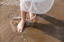 Barefoot In A White Dress Feeling The Incoming Sea Surf And The Sand. Wanderlust, Beach Wedding And Lifestyle Concept.