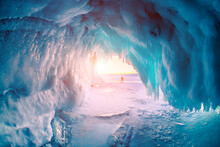 Ice Cave On Baikal Lake In Winter. Blue Ice And Icicles In The Sunset Sunlight. Olkhon Island, Baikal, Siberia, Russia. Beautiful Winter Landscape.