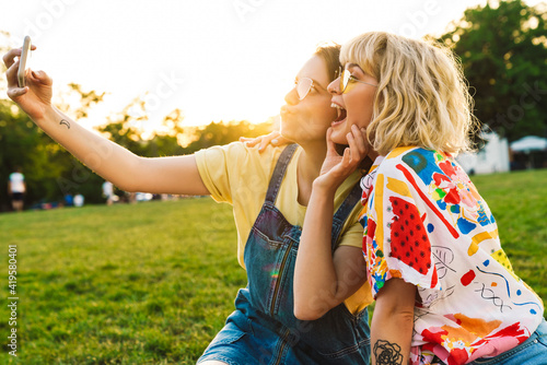 Fényképezés Image of amusing two women in sunglasses taking selfie on smartphone