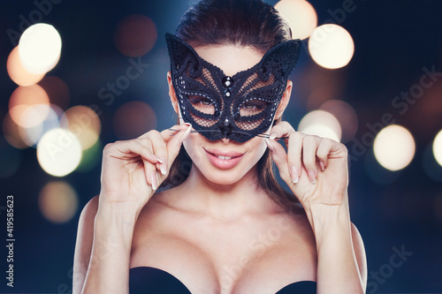 Foto Sexy brunette woman holding mustache in catwoman mask