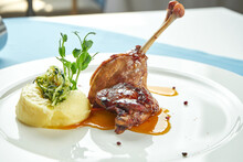 Duck Leg Confit With Sweet Sauce Garnished With Mashed Potatoes In A White Plate On A Blue Tablecloth