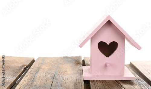 Canvastavla Beautiful bird house with heart shaped hole on wooden table against white backgr