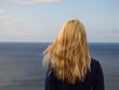 Dziewczyna z blond włosami patrze daleko w horyzont nad morzem