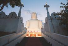 Steps Leading Up To The Giant White Buddha Statue Illuminated At Night At Sri Maha Bodhi Viharaya, A Buddhist Temple At Bahirawakanda In Kandy, Sri Lanka.
