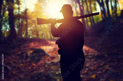 Photographie Male hunter silhouette with a gun at sunset