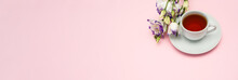 Purple Flowers And A White Coffee Cup On A Pink Background. A Beautiful Banner With Space To Copy.