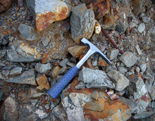 Steel Chisel Edge Rock Pick, Geologist Tool Over Natural Rocks Background