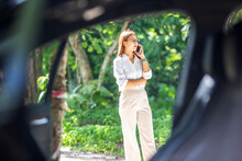 A Woman In A Car Broke Down On The Road Trying To Fix The Problem And Called A Car Repair Shop Or Someone Close To Help.
