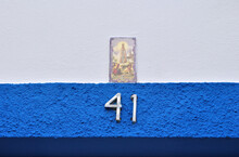 Blue Textured Wall With Number 41 And Decorative Ceramic Plaque