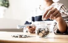 A Woman Is Putting Coins In A Jar With A Lot Of Coins Inside, She Is Managing To Divide Her Money To Save Money And Invest It To Make It Grow Even More. Concept Of Saving Money And Investing.