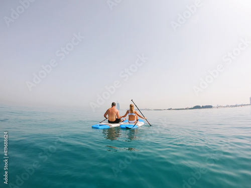 Платно Active Couple on the paddle boards with a view on Burj Al Arab