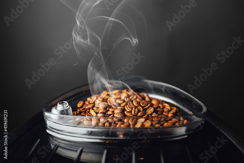 Leinwand Poster fresh roasted coffee beans with smoke in coffeemaker bean container, close-up vi