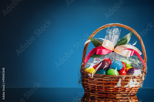 Canvas Print Easter gift basket with multicolor eggs, blue background with copy-space