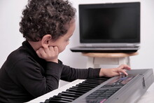 Boy Playing The Piano Keyboard On White Background Stock Photo