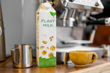 Packaging Of Vegetable Milk Near Pincher, A Cup Of Coffee And Coffee Machine On Wooden Table Top On The Kitchen. Organic Nut Dairy, Alternative Drink.