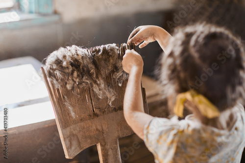 Fototapeta A girl is working with an artificial wooden handmade wool carding comb. Handmade manufacturing concept obraz
