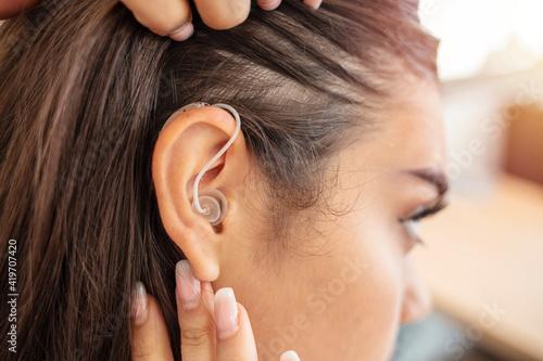 Slika na platnu Woman adjusting hearing aid indoors