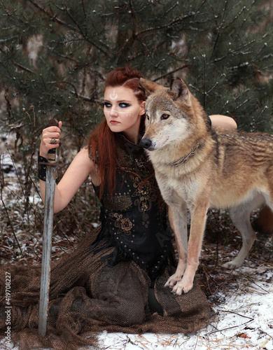 Fototapeta Warrior girl with wolf in winter forest