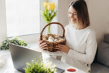 Young Woman Celebrating Easter Distantly With Friends And Relatives. Making Online Video Call And Showing Decorated Eggs In Straw Basked. Traditional Holidays During COVID Lockdown, New Normal Concept