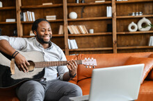 A Happy African-American Guy Is Playing Guitar In Front Of A Laptop At Home, A Multiracial Man Performs Online, Streaming. A Black Man Is Learning Playing Guitar With A Video Classes On The Computer