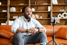 A Handsome African-American Guy Is Talking To Followers, Streaming Online, A Man Sitting On The Couch And Speaking Into A Smartphone On The Tripod In Front Of Him. Blogger And Vlogging Concept.