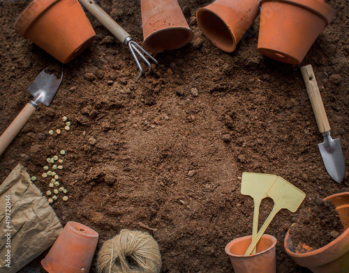 Photo Clay terracotta pots and garden tools on soil, copy space for text, top view, sp
