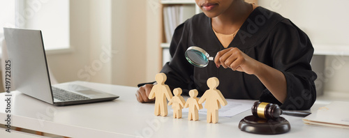 Fotografia African american judge looking through magnifying glass at wood family figure making decision on children custody