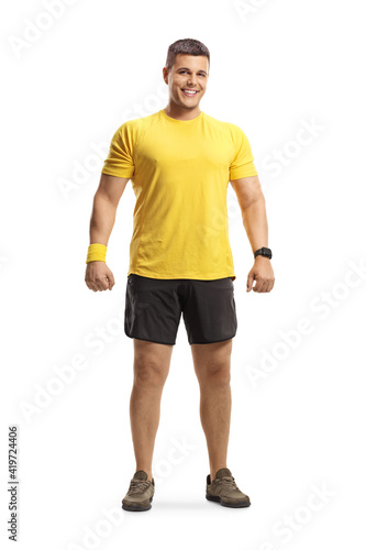Obraz na plátně Full length portrait of a young man in sportswear smiling at camera
