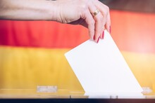 Woman Voting On Elections In Gemany. Germany Flag Background.