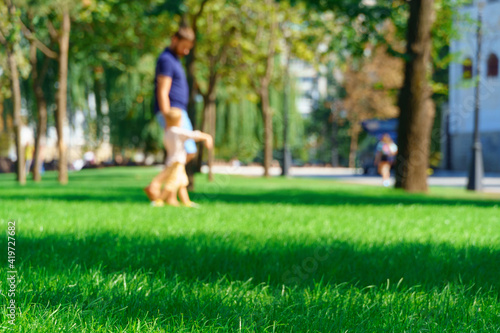 Obraz na plátně people walking and children playing in a city park on a summer day, green lawns