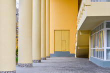 Fragment Of Facade Of A Light Yellow Building With Big Round Columns.  Selective Focus.