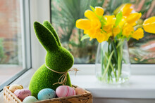 Easter Bunny Rabbit Statuette In Straw Basket With Colored Eggs On The Windowsill With Fresh Spring Tulips And Daffodils Flowers Bouquet On The Background. Happy Easter. Selective Focus. Copy Space.