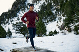 Determined young male athlete running on footbridge while listening music during winter